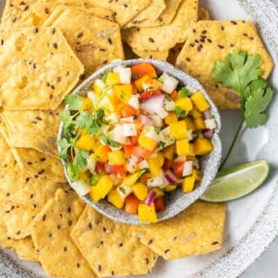 A bowl of multi grain chips with a dish of salsa in the middle.