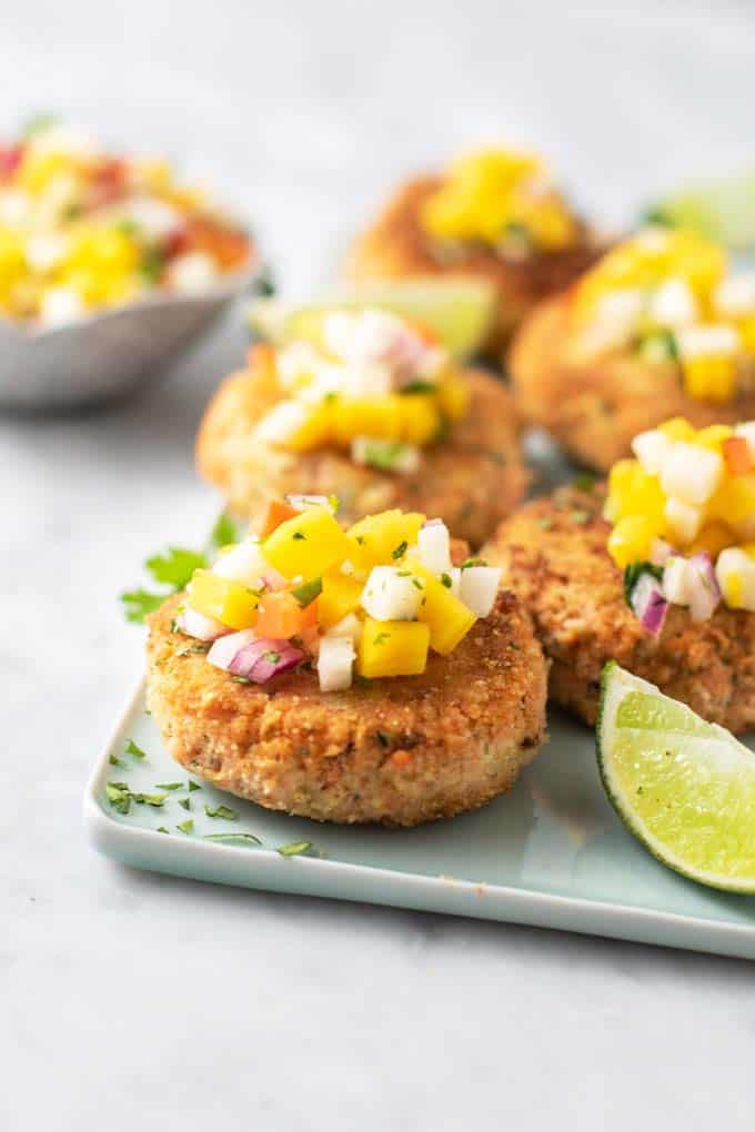 A straight on view of thick fried salmon patties topped with mango salsa.