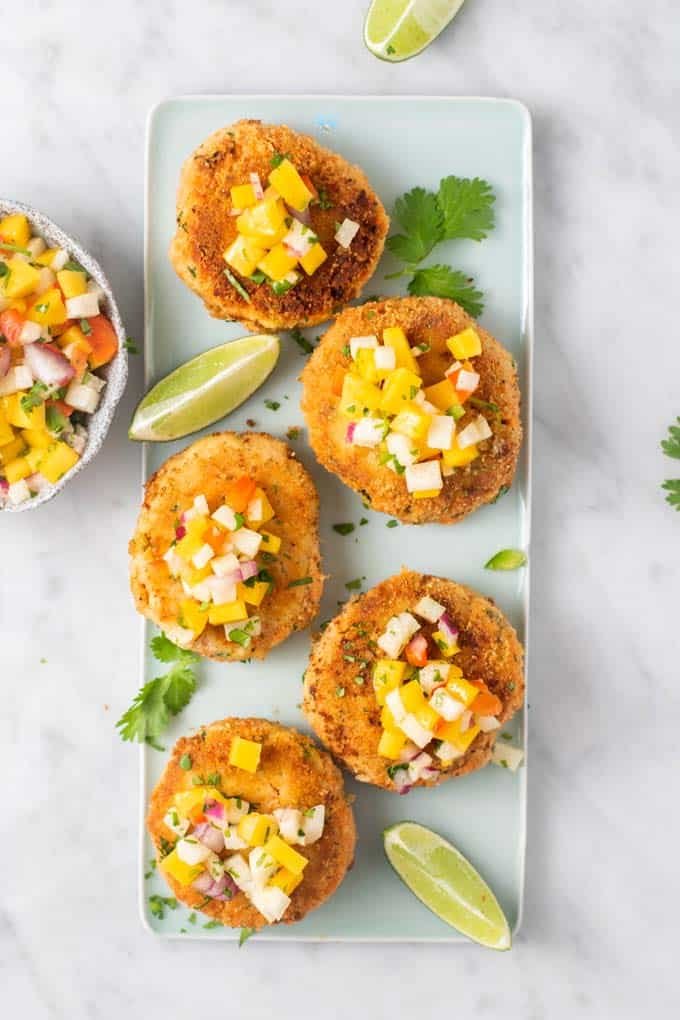 A blue plate with salmon patties topped with mango salsa and garnished with cilantro.