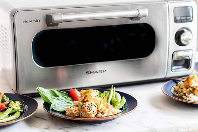 A sharp superheated steam countertop oven with 4 plates of sweet and sour chicken in front.