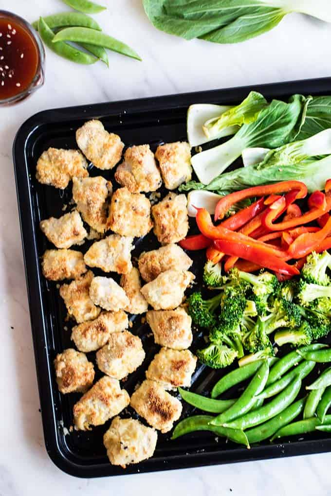 A sheet pan with crispy chicken pieces and Asian style vegetables.