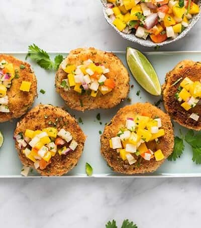 A blue plate with zucchini salmon patties topped with mango salsa.