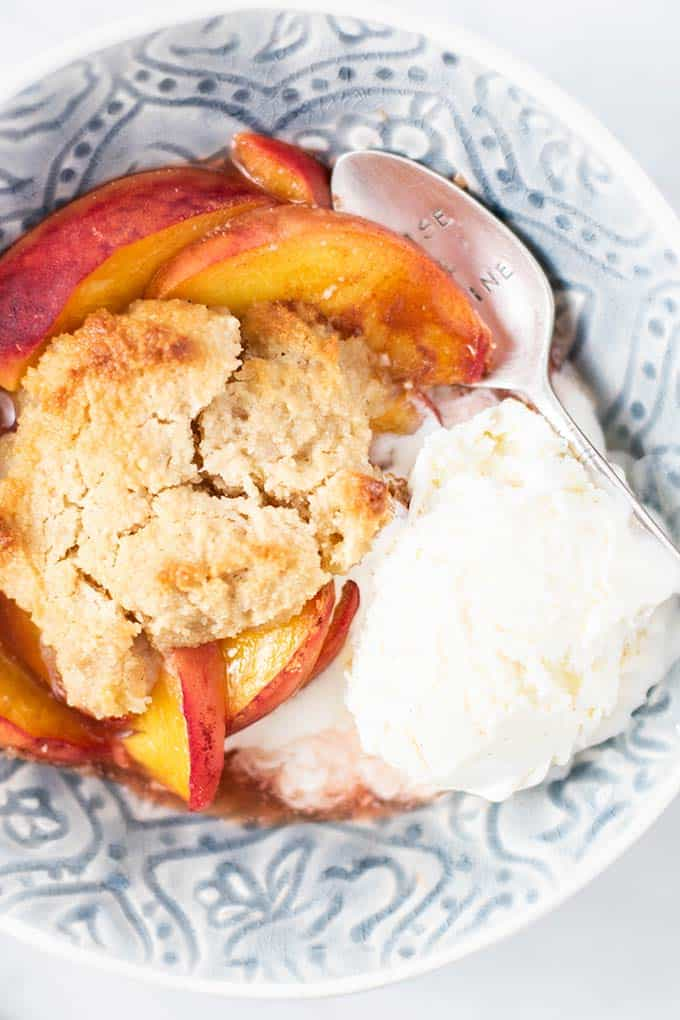 A blue bowl with a serving of peach cobbler with a scoop of vanilla ice cream.