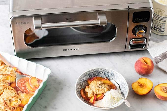 Sharp Superheated Steam Countertop Oven with a bowl of peach cobbler on the counter.