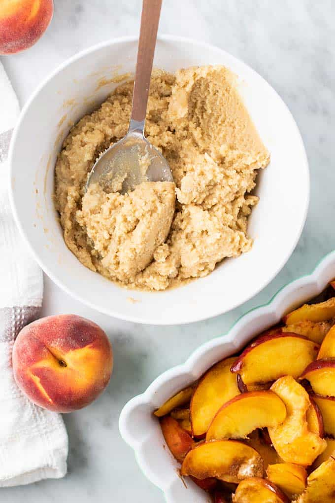 A bowl of almond flour biscuit dough sitting next to a baking dish filled with peaches.