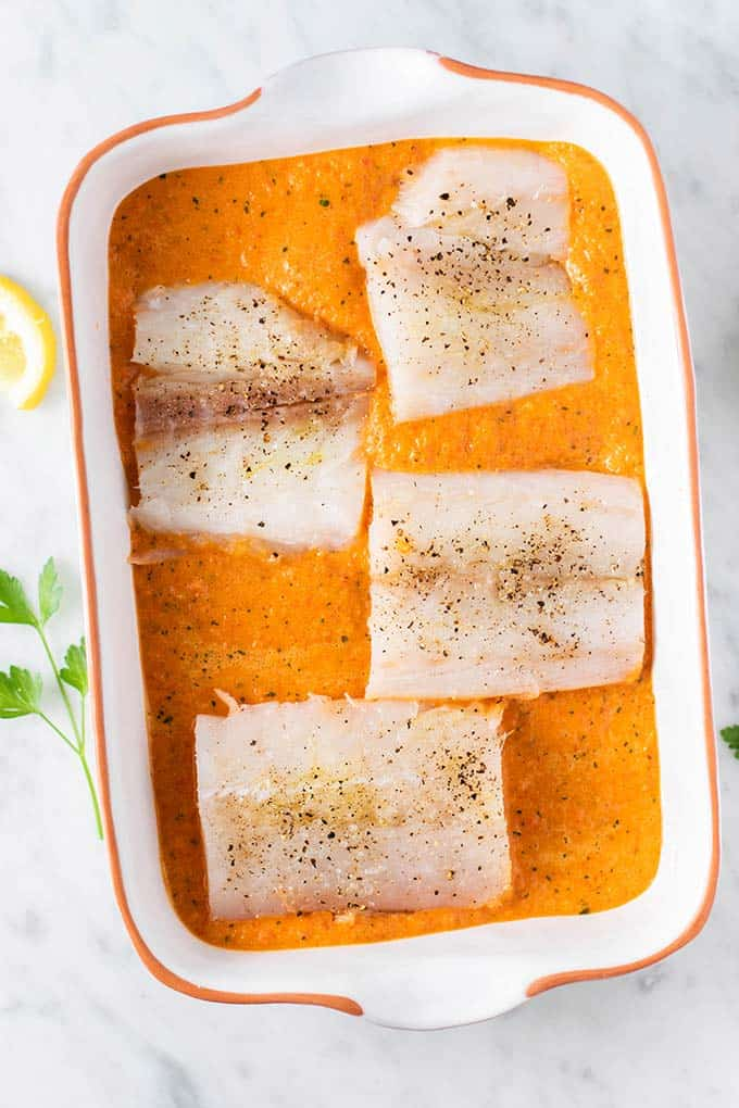 Four uncooked cod fillets in a baking dish filled with red pepper sauce.