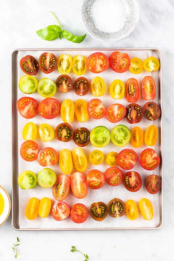 Fresh tomatoes spread out on a baking tray ready to be baked.