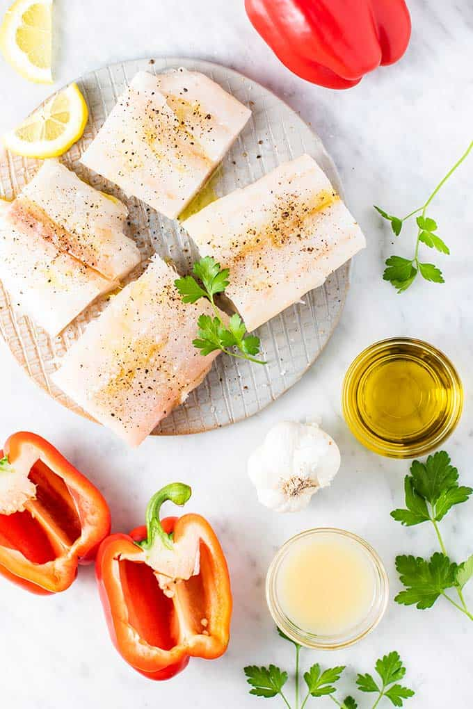 The ingredients needed for this recipe, including cod fillets, red peppers, and parsley.