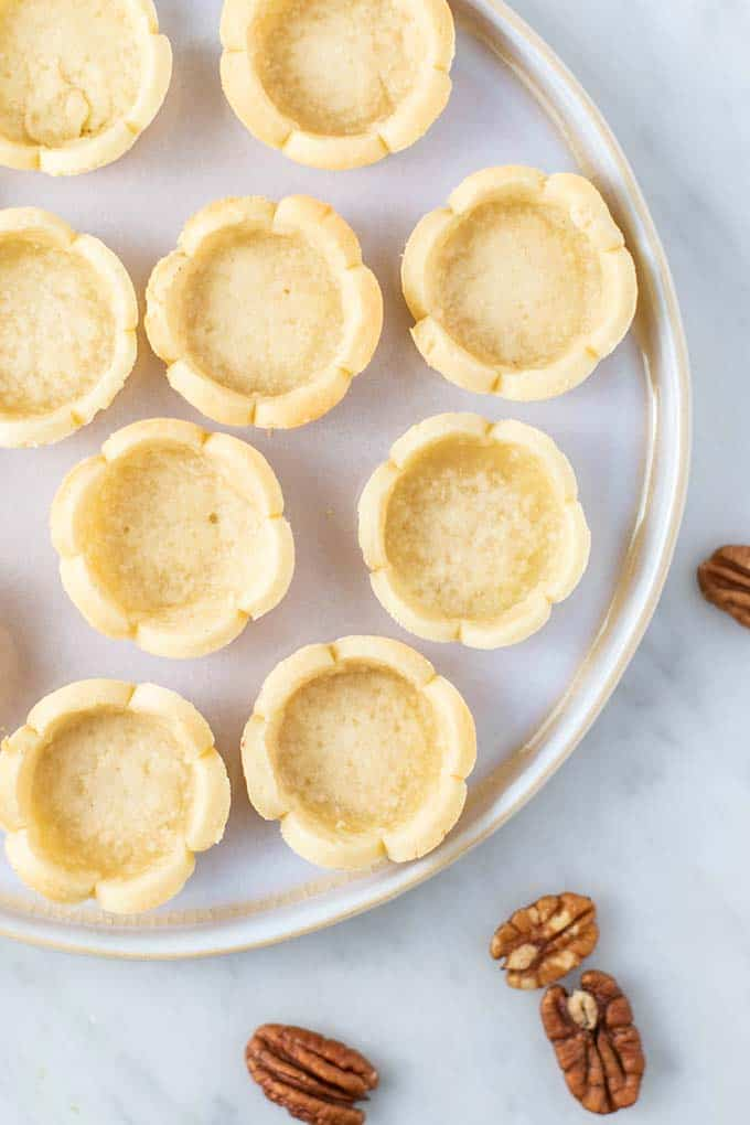 A plate of plain almond flour pie crusts baked into mini pie shapes.