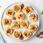 A top view of a plate of mini pumpkin pies topped with pecans.