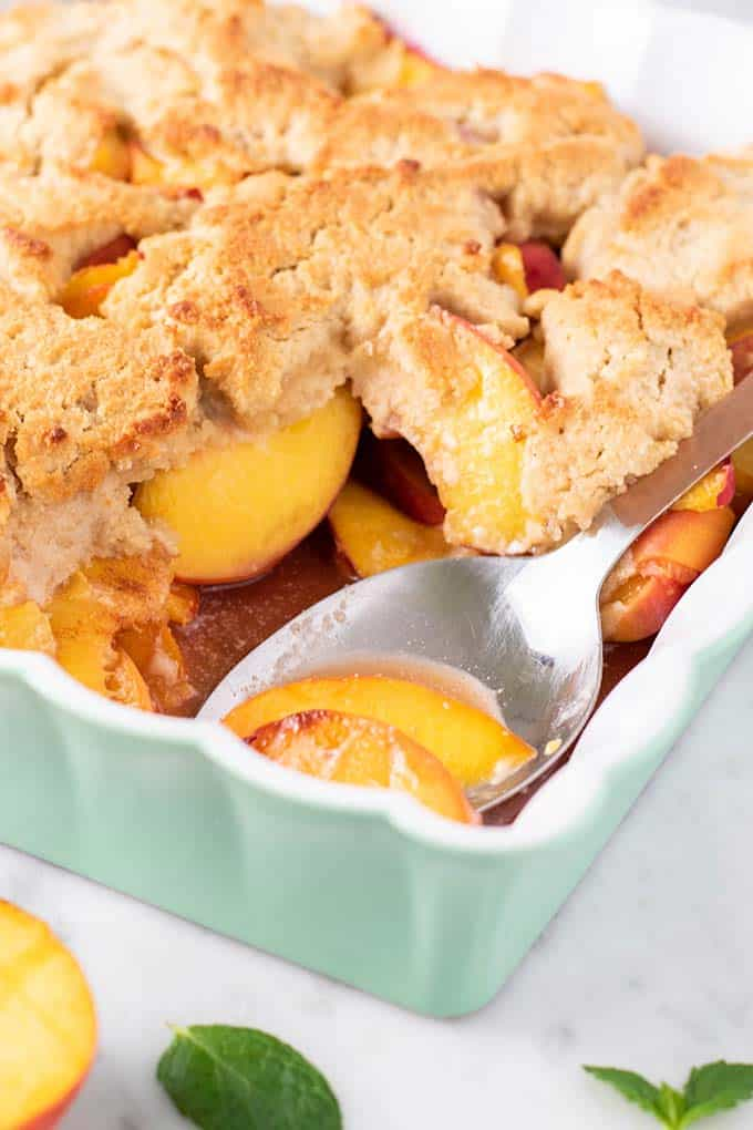 A spoon scooping up some peach cobbler.