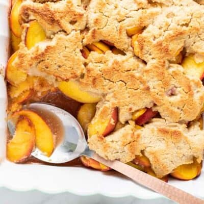 A baking dish filled with a golden brown peach cobbler with one scoop taken out.