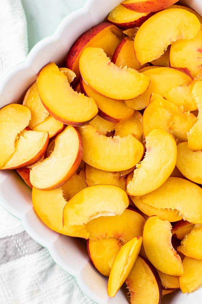 A baking dish filled with thinly sliced peaches.