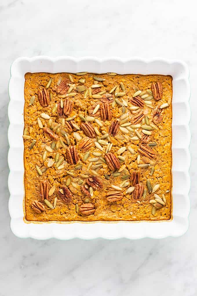 A healthy baked oatmeal recipe shown baked in a square dish, topped with pecans and pumpkin seeds.