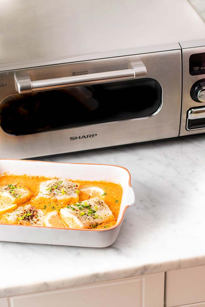 A Sharp Superheated Steam Countertop Oven with a pan of baked cod.