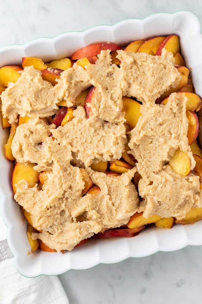 A baking dish filled with peaches and topped with an almond flour biscuit dough.