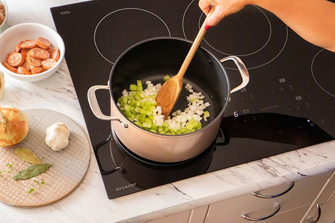Sauteing the onions, garlic and celery in the pot.