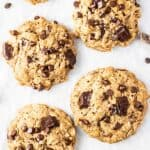 Lots of vegan oatmeal cookies shown with extra chocolate chips sprinkled around them.