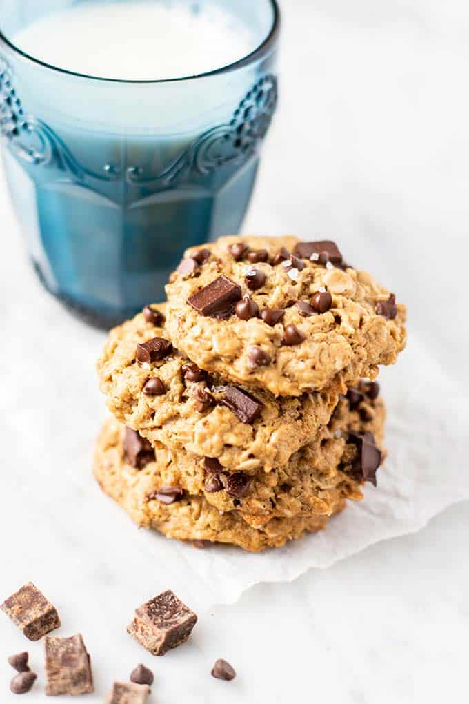 Three vegan oatmeal cookies in front of a glass of milk.