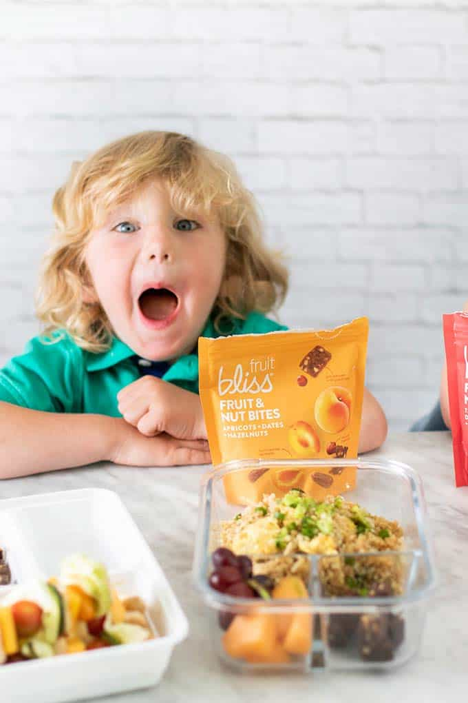A little boy excited to be helping pack his school lunch.