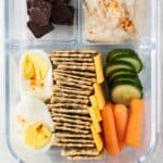 A hummus box with crackers, a hard boiled egg, cheese, vegetables, hummus, and some chewy fruit and nut bites.