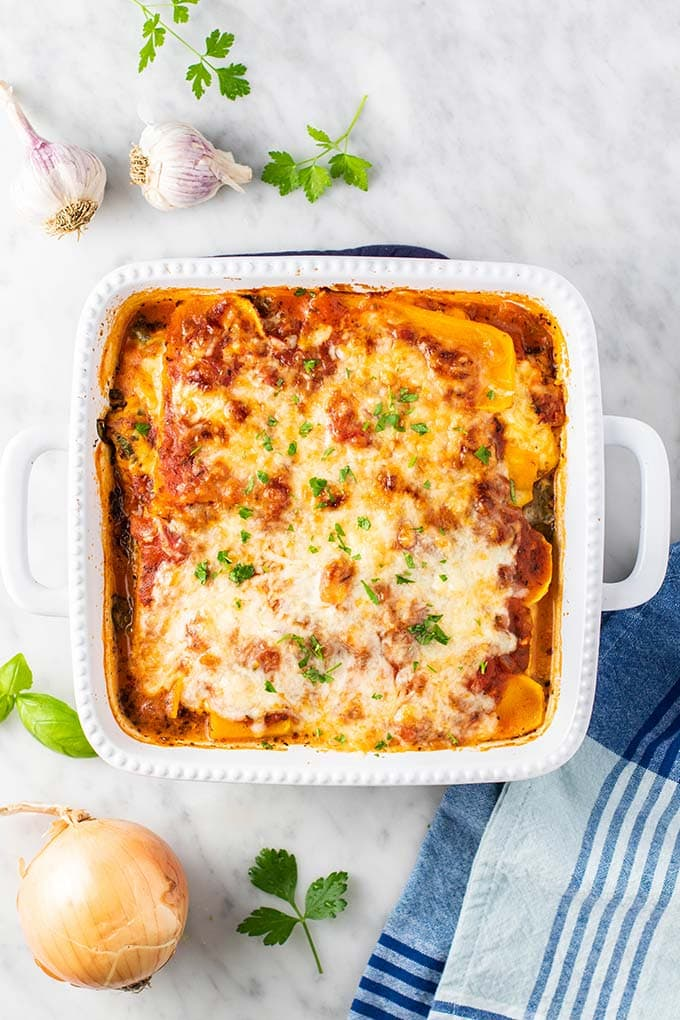 A baked butternut lasagna in a white casserole dish.