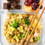 A bento box with some broccolil and quinoa fried rice, some cantaloupe and grapes, and some chewy fruit and nut bites.
