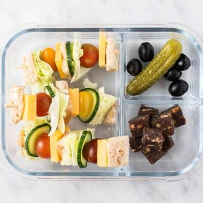 A lunch box with cheese sandwich skewers, pickles, and fruit.