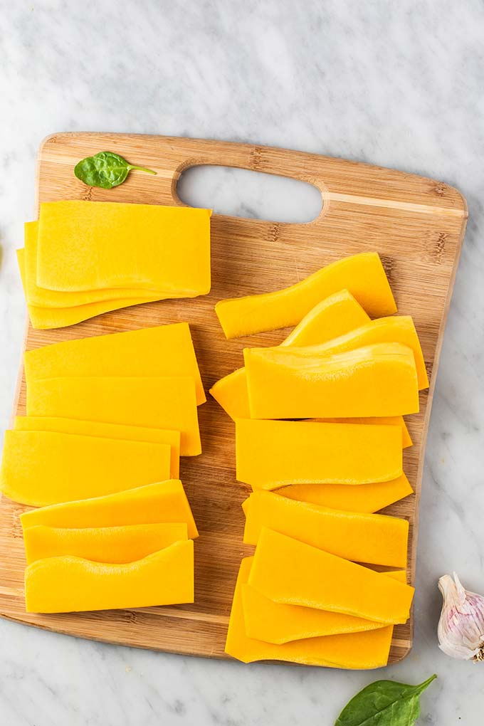 A cutting board with thinly sliced butternut noodles.