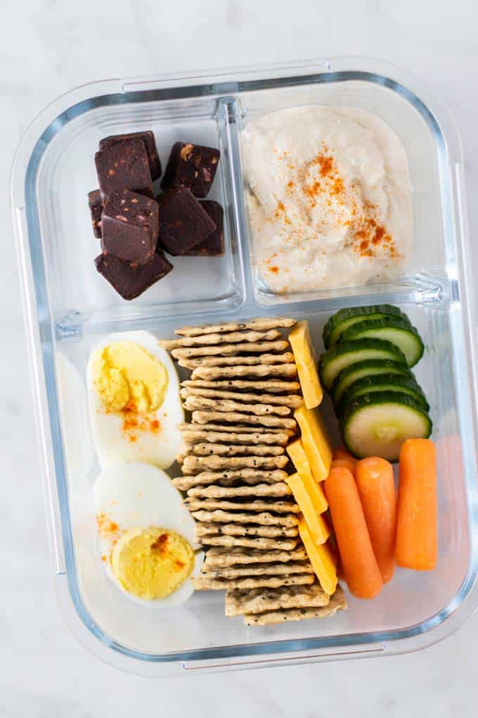 A hummus box with crackers, a hard boiled egg, cheese, vegetables, hummus, and fruit and nut bites.