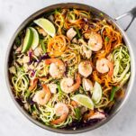 A large skillet filled with veggie noodles, chicken and shrimp, garnished with sunflower seeds and limes.