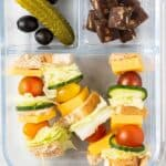 A bento box with cheese sandwich skewers, a pickle, some olives, and some chewy fruit and nut bites.