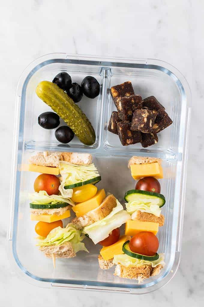 A glass bento box with sandwich skewers, a pickle, some olives, and some chewy fruit and nut bites.