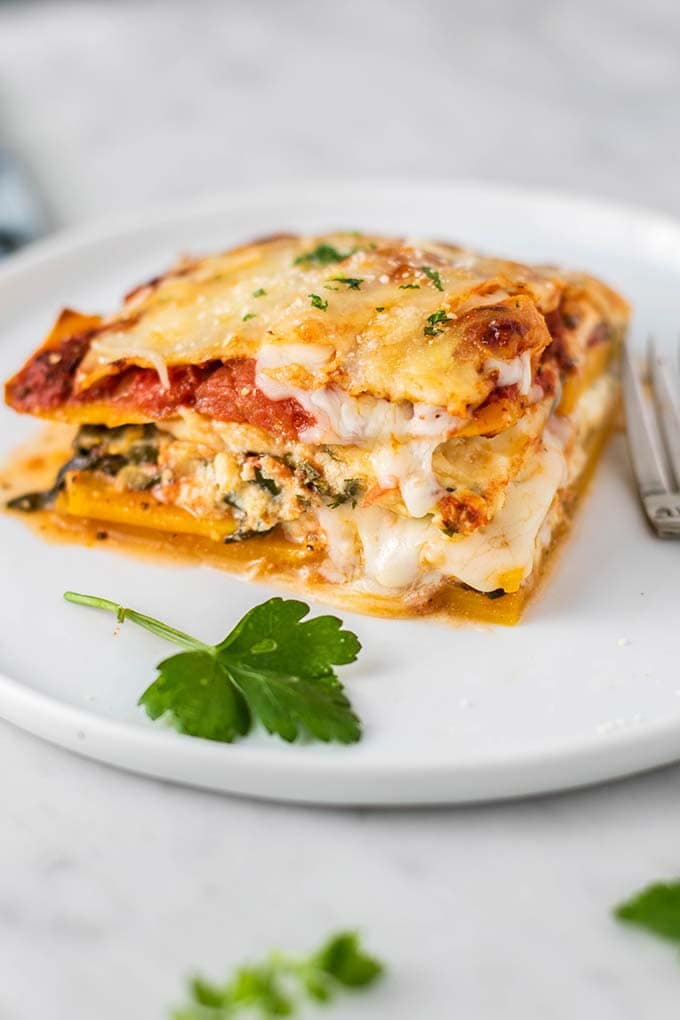 A slice of butternut lasagna with cheese oozing out.