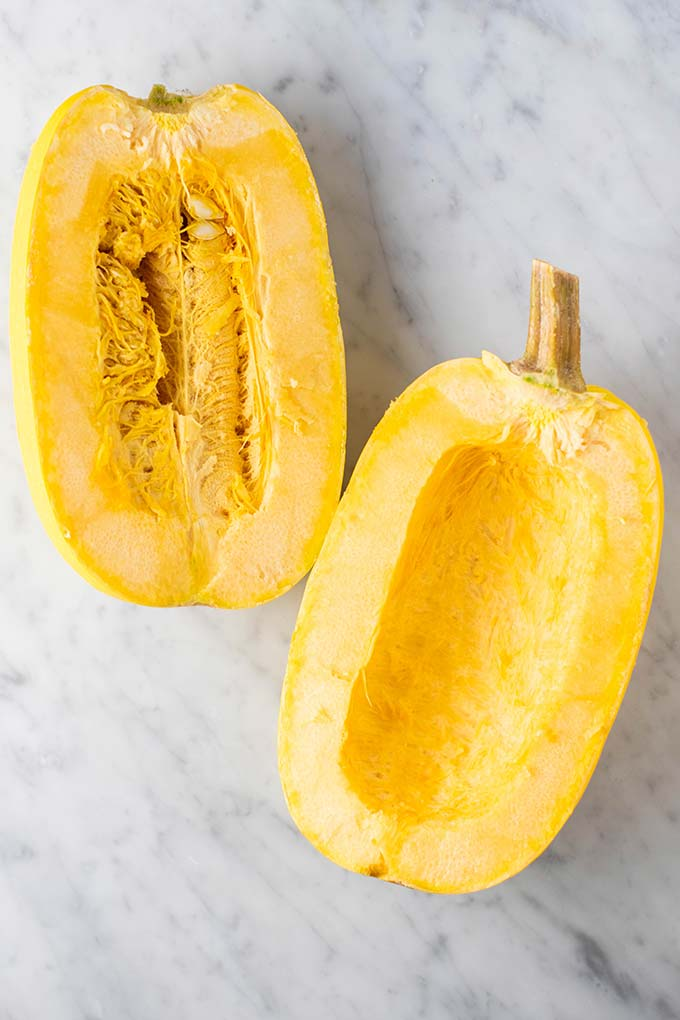 A spaghetti squash cut in half showing how to prepare it to bake.