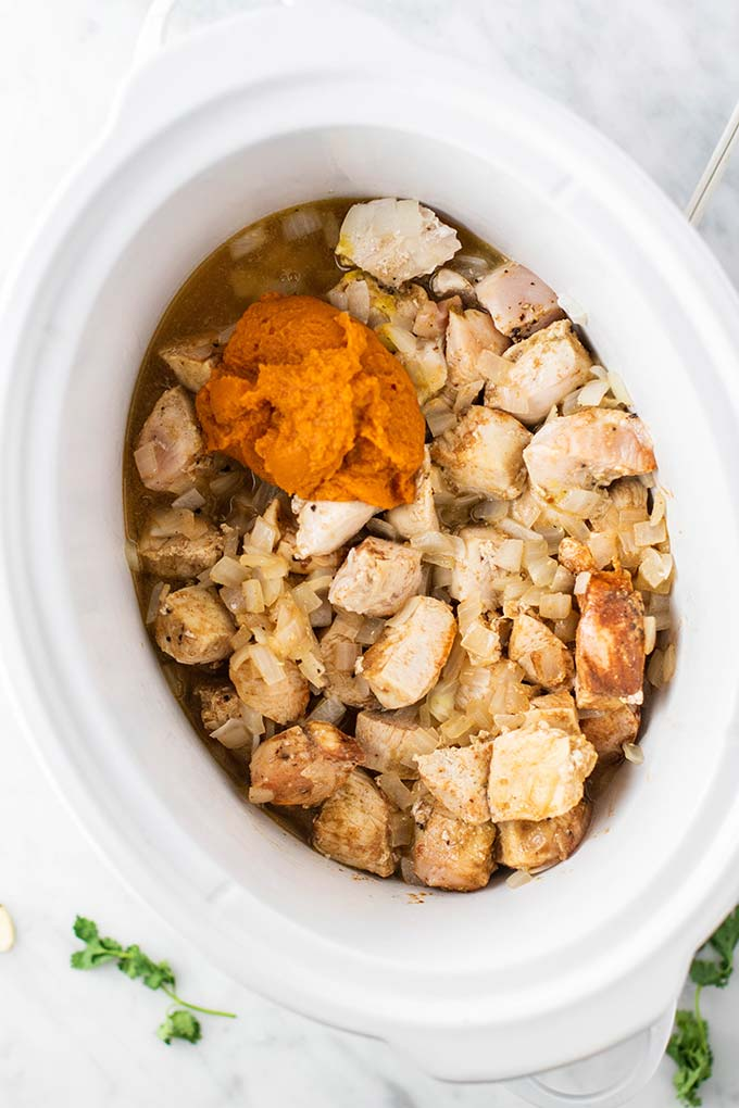 A crockpot with browned chicken, pumpkin, and broth.