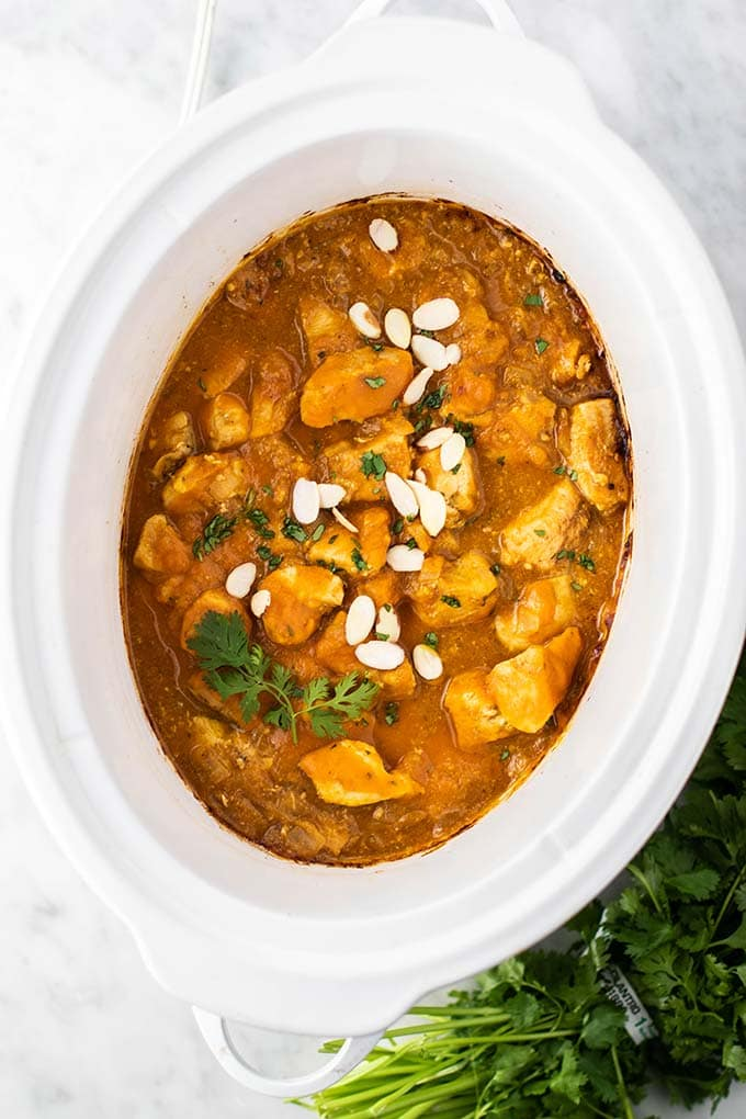 A white crockpot filled with chicken simmered in a spicy pumpkin sauce.