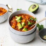 A bowl filled with Whole30 chili garnished with avocado and cilantro.