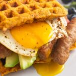 A close up shot of an egg yolk dripping out of the side of a sweet potato waffle breakfast sandwich.