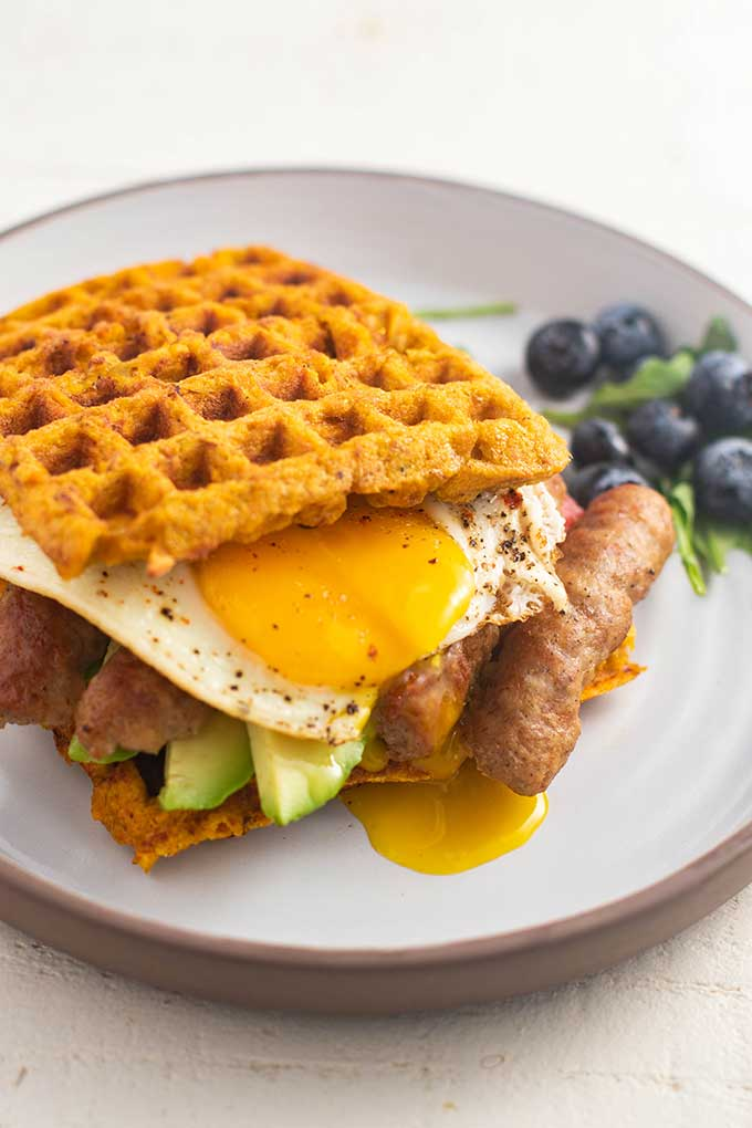 A sweet potato waffle breakfast sandwich with a broken egg yolk dripping out of the side.