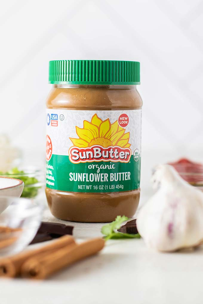 A jar of organic sunbutter surrounded by the rest of the ingredients for this dish.
