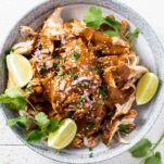 A bowl of slow cooker chicken mole garnished with limes.