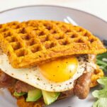A breakfast sandwich made with gluten free sweet potato waffles, sausage, and eggs.