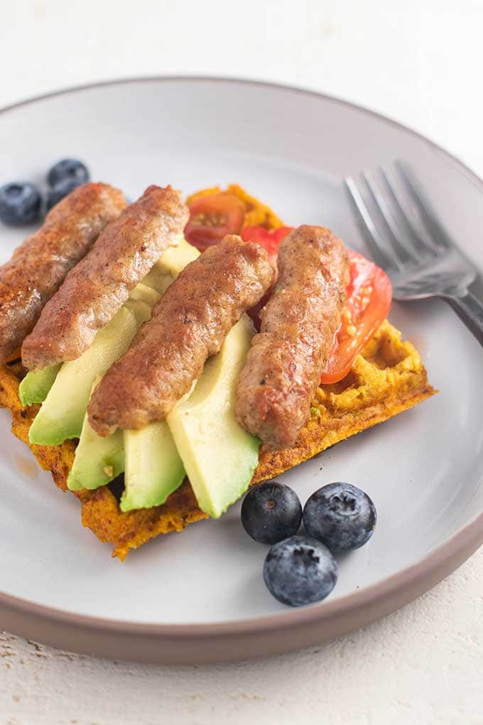 A sweet potato waffle with sliced avocado, sausage, and cherry tomatoes.