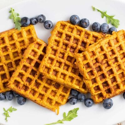 A white plate with sweet potato waffles stacked on it, surrounded by blueberries.