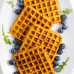A plate showing sweet potato waffles close up with arugula and blueberries.