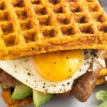 A close up look at a sweet potato waffle breakfast sandwich from the side to show the fillings.