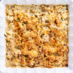 A square baking dish filled with cheesy cauliflower topped with toasted breadcrumbs.