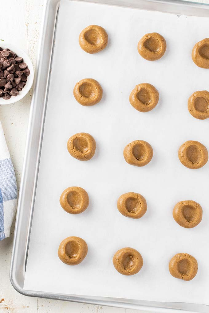 A cookie sheet with cookie dough balls with thumbprint indents.