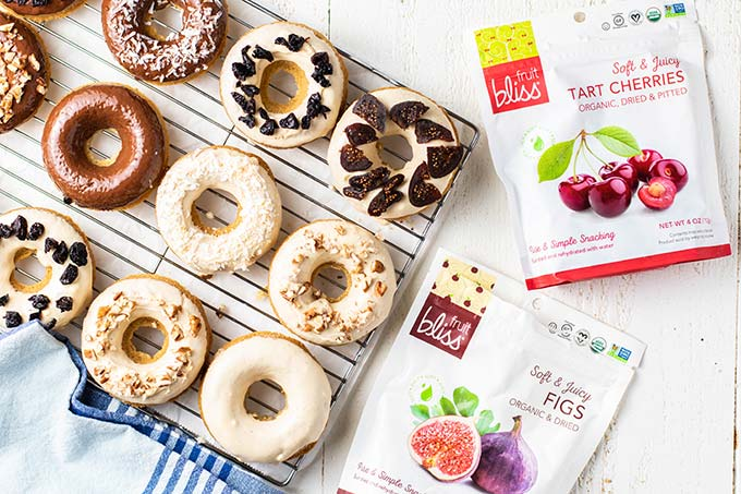 A cooling rack covered in decorated donuts, next to bags of Fruit Bliss Organic Dried Fruit.